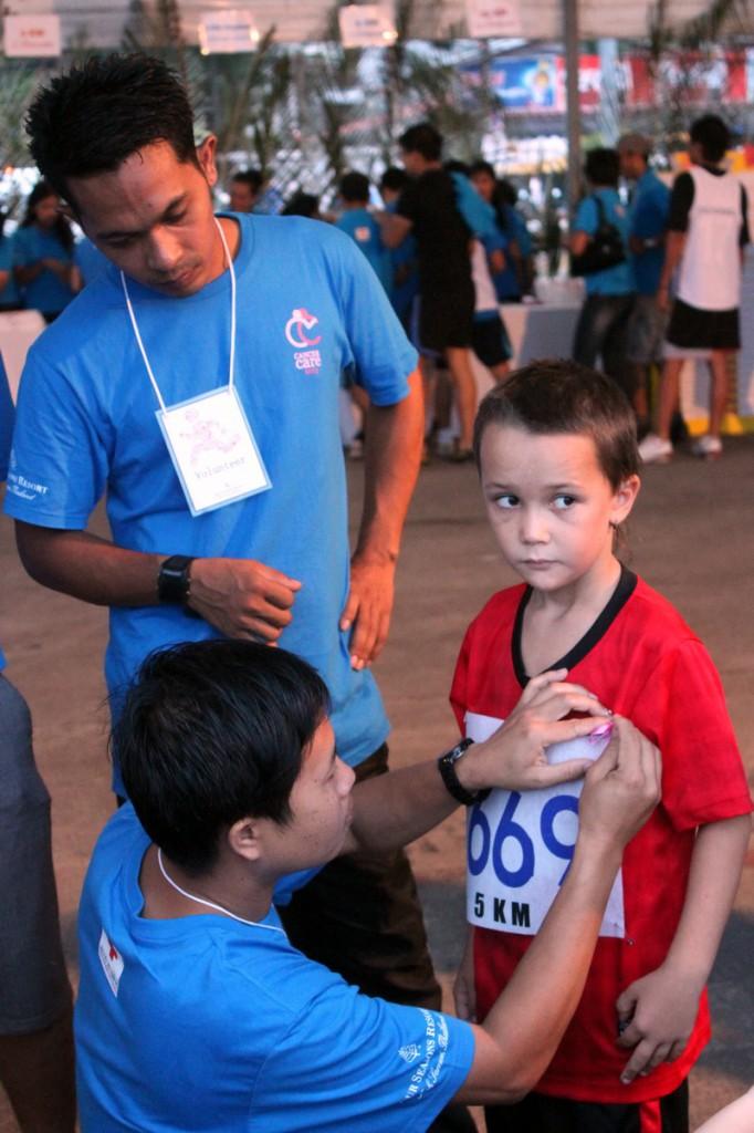 Волонтеры помогают Арсению прикрепить номер к футболке